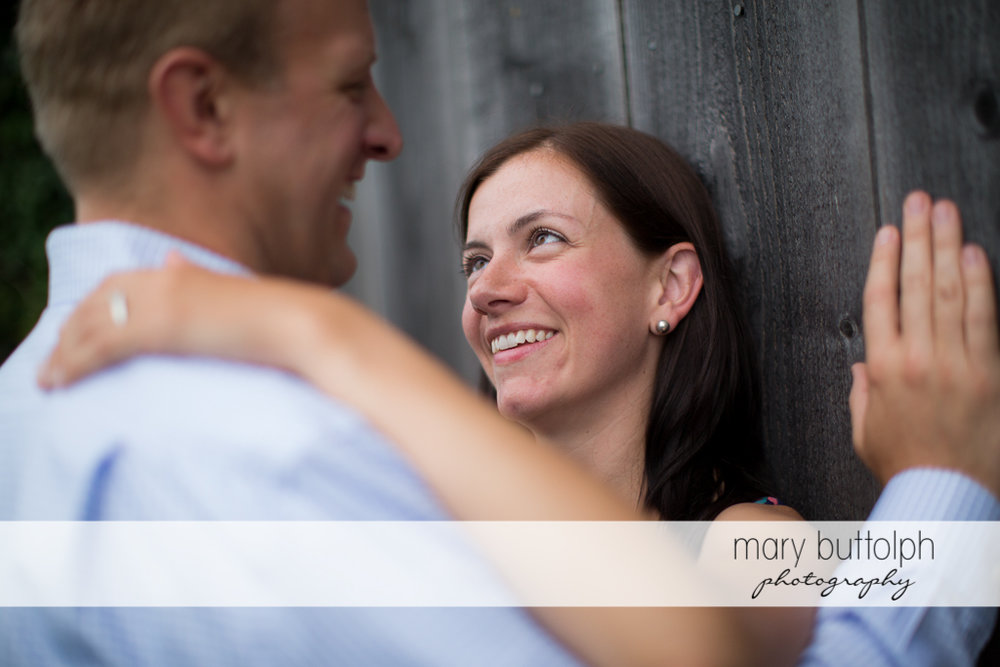 Couple get romantic near a wooden structure at Skaneateles Farm Engagement
