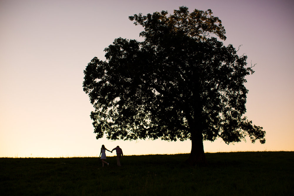 Couple hold hands while walking in the field at Skaneateles Engagement
