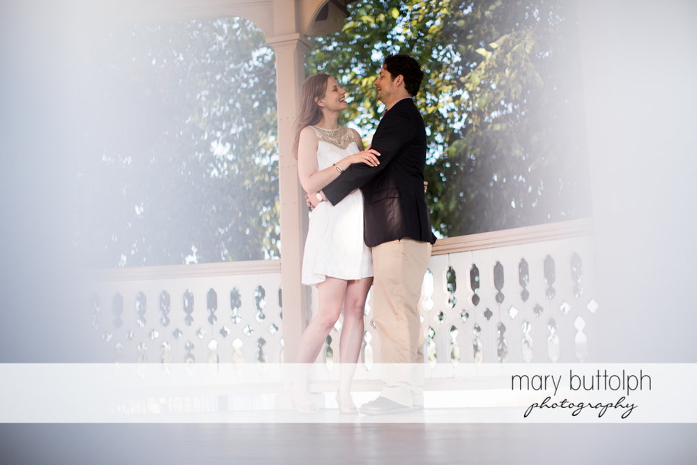 Couple embrace in the porch at Skaneateles Engagement