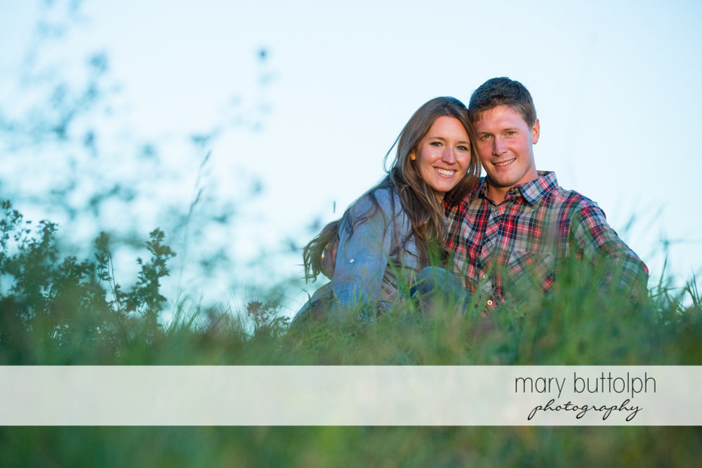 Couple take a break in the field at Aurora Engagement