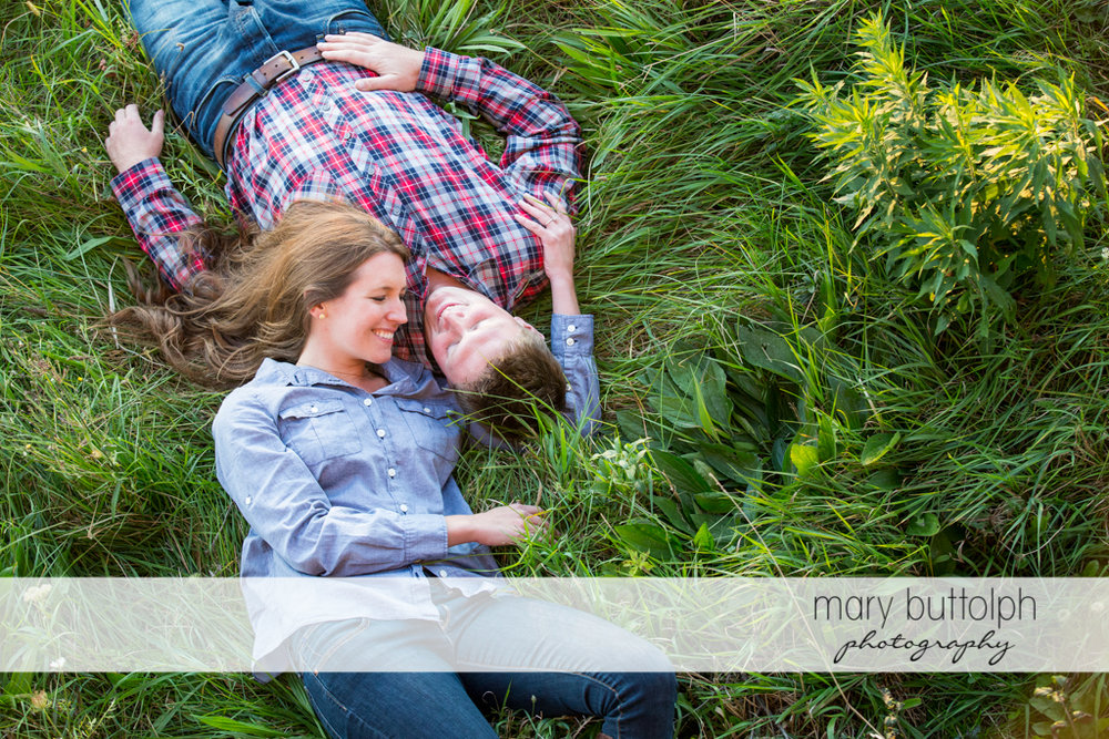 Couple lie on the grass in the field at Aurora Engagement