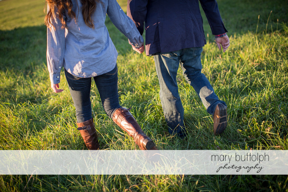 Couple cross the field together at Aurora Engagement