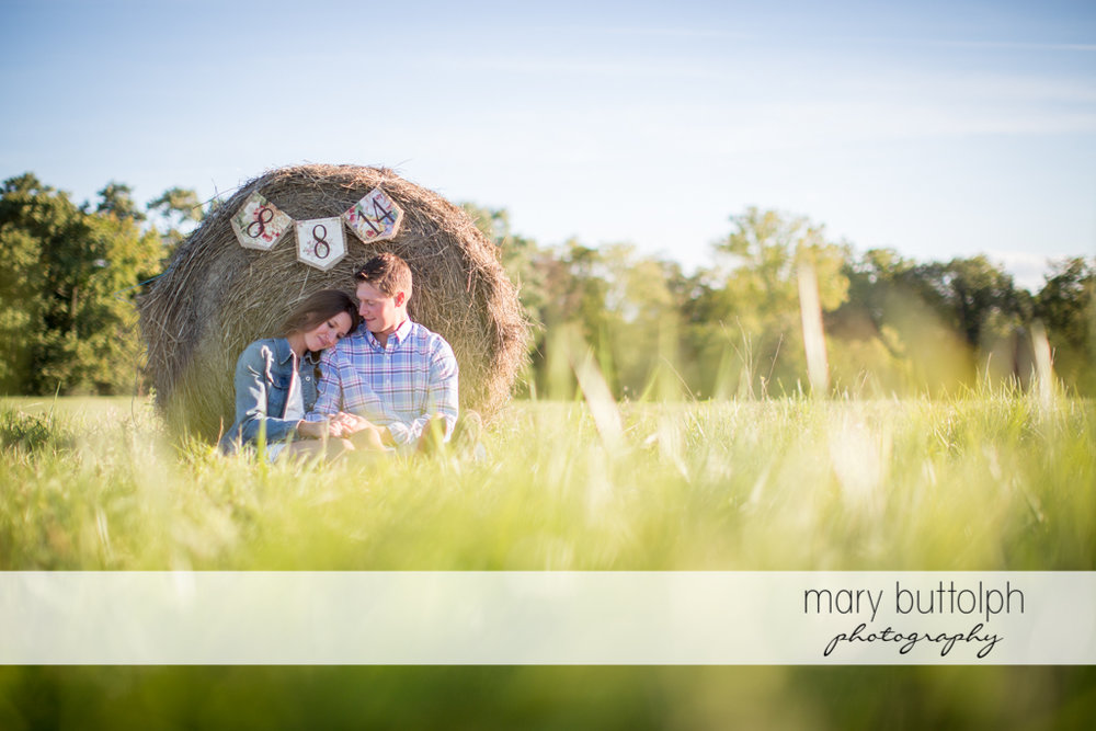 Couple sit near a haystack showing their wedding day at Aurora Engagement