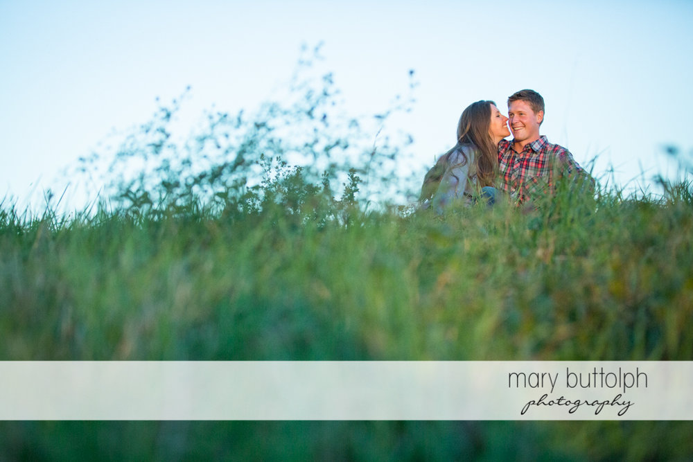 Couple relax in the field at Aurora Engagement