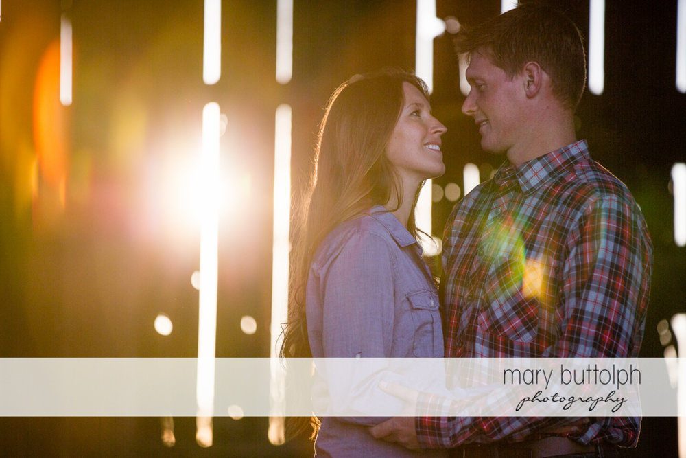 Couple pose inside a barn as the sun sets at Aurora Engagement