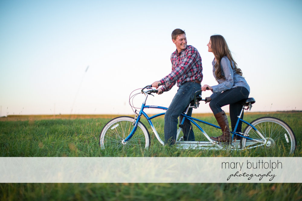 Couple ride a bicycle on the field at Aurora Engagement