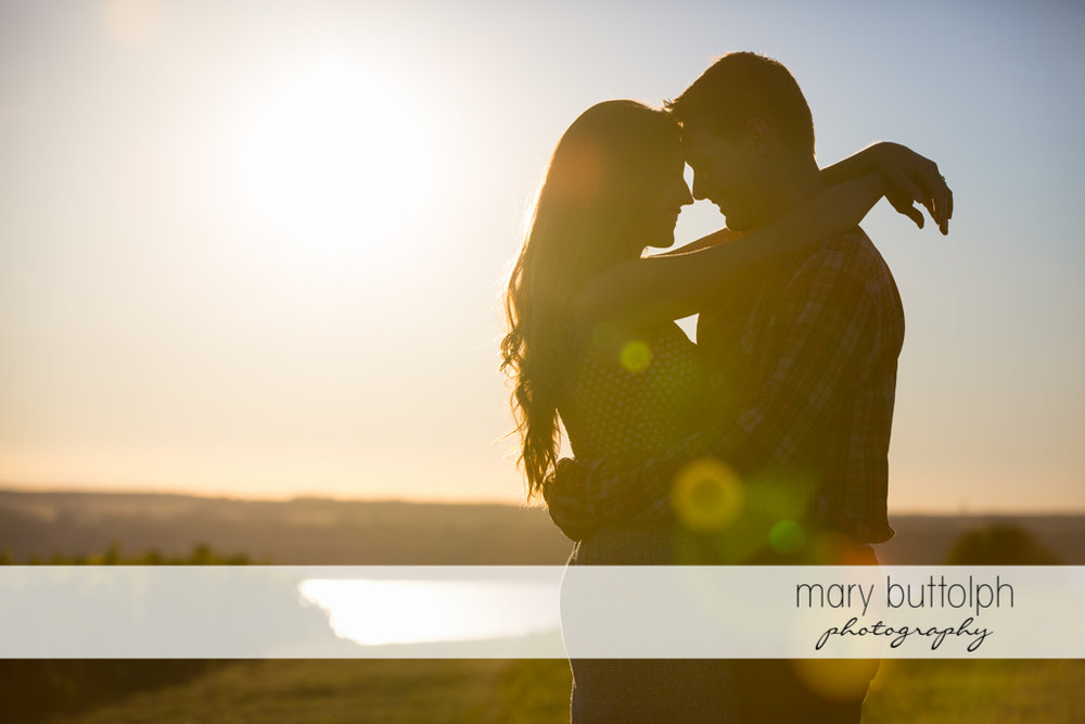 Couple embrace in the field as the sun goes down at Aurora Engagement
