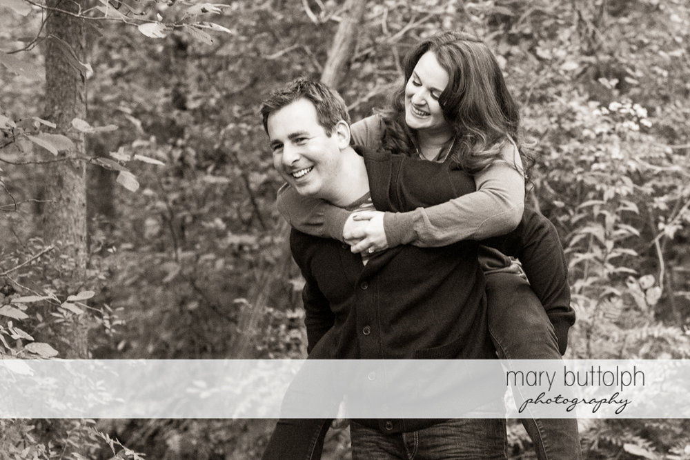 Man gives woman a piggyback ride in the woods at Beaver Lake Nature Center Engagement