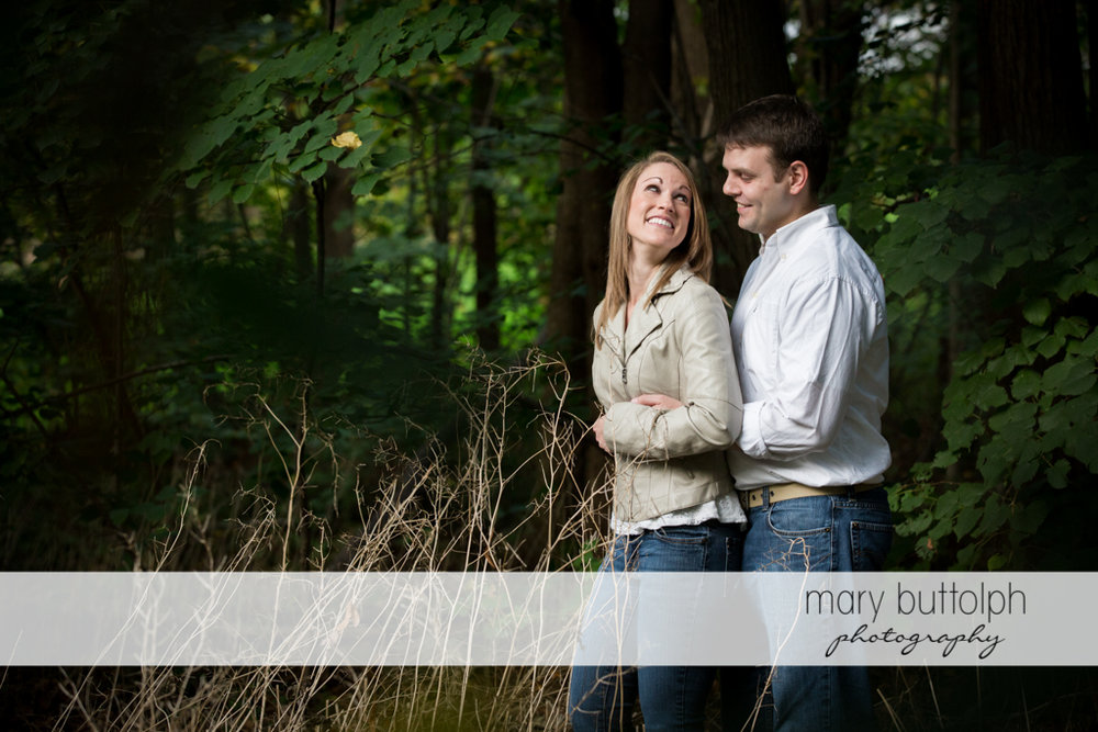 Couple lovingly glance at each other in the woods at Skaneateles Engagement
