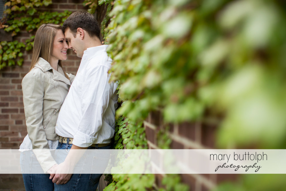 Couple in a quiet moment near a brick wall in the garden at Skaneateles Engagement