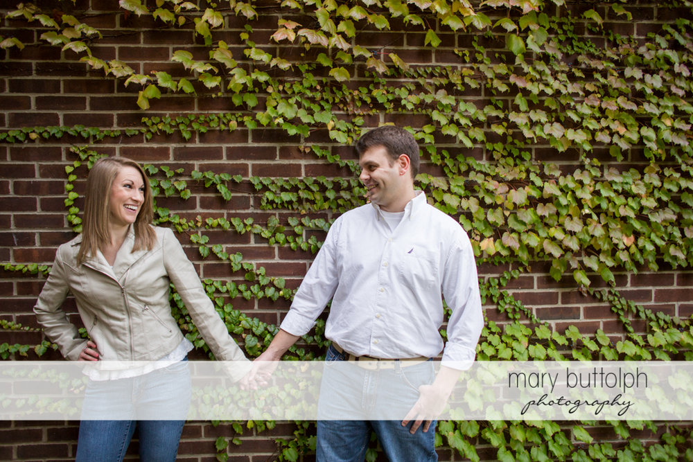 Couple hold hands in front of a brick wall at Skaneateles Engagement