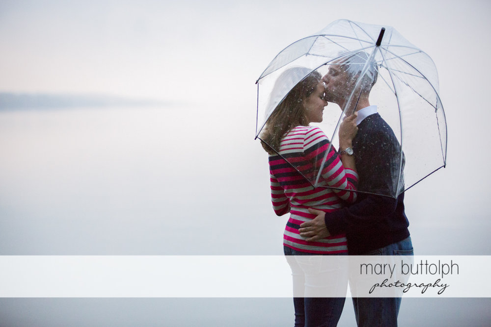 Couple share an umbrella in the rain at Syracuse University Engagement