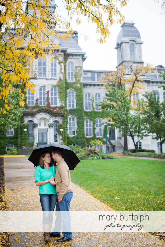 Couple with an umbrella stand in front of a building at Syracuse University Engagement