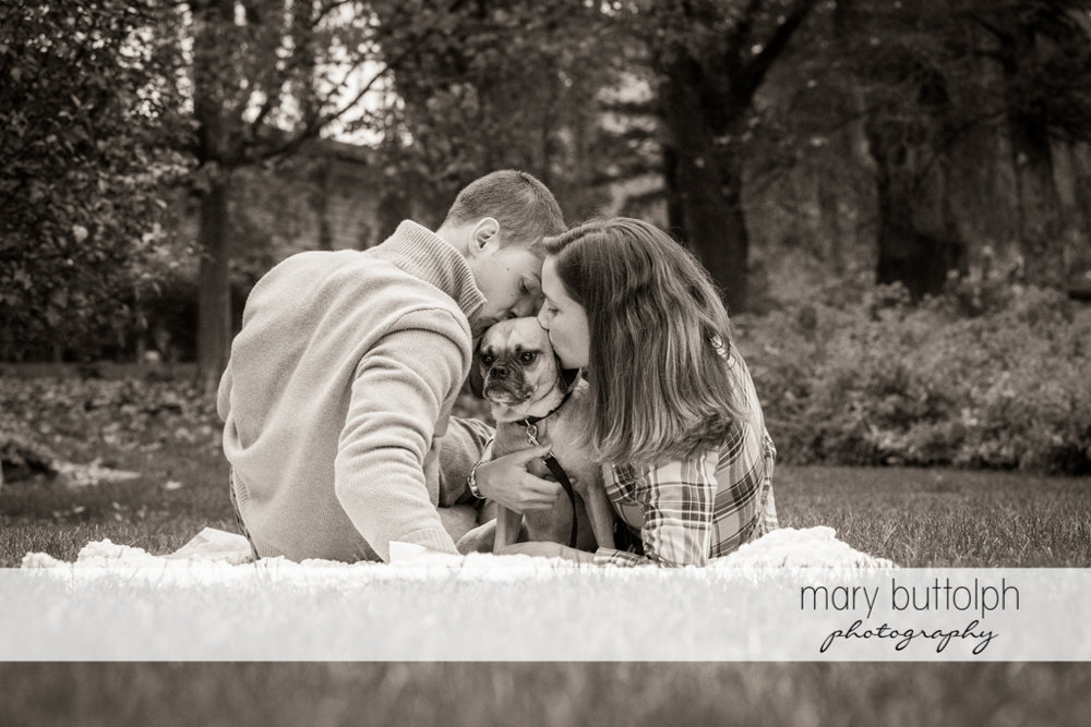 Couple kiss their pet dog while sitting on the grass at Syracuse University Engagement