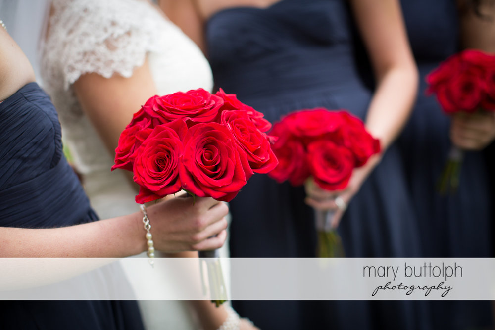 Bride and bridesmaids holding roses at Traditions at the Links Wedding