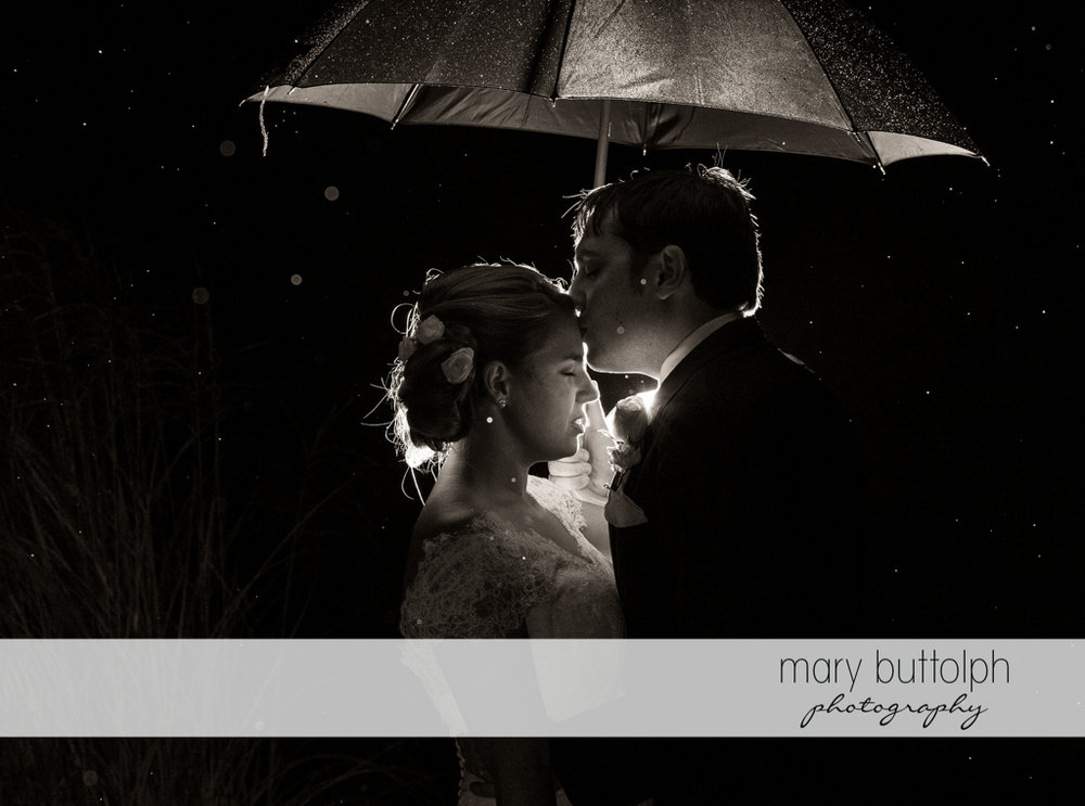 Couple get romantic in the rain at Traditions at the Links Wedding