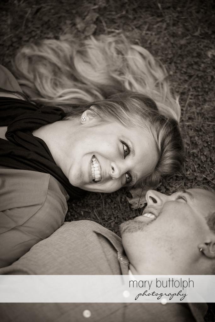 Couple lie on the grass at Watkins Glen Engagement