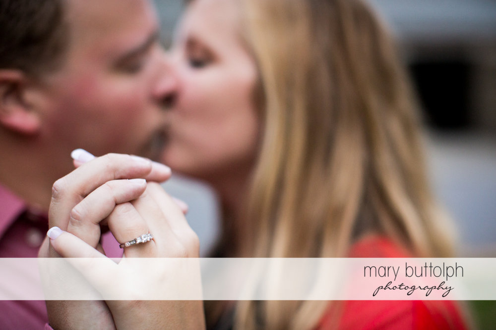 Woman's engagement ring is clearly visible as the couple kiss at Watkins Glen Engagement