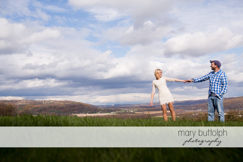 Couple enjoying the view in the field at Beak & Skiff Apple Orchards Engagement