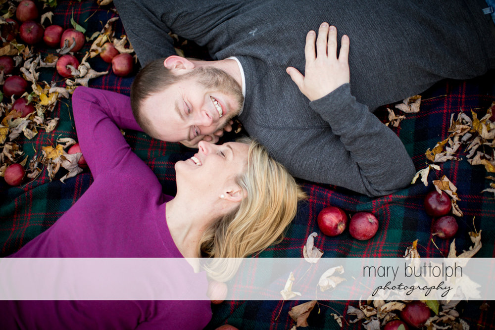 Couple lie on a blanket with apples at Beak & Skiff Apple Orchards Engagement