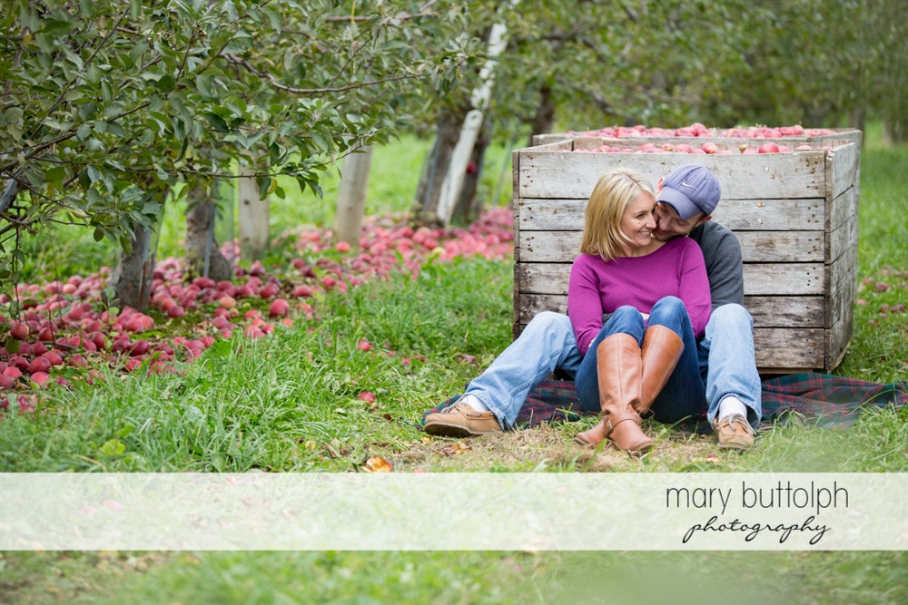 Couple sit next to a crate full of apples in the garden at Beak & Skiff Apple Orchards Engagement