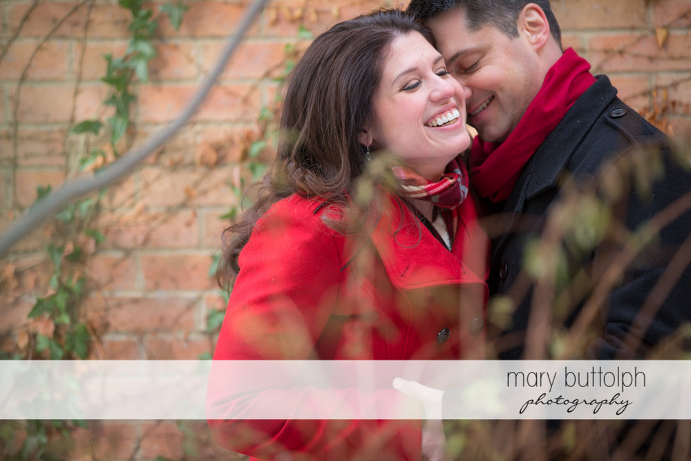 Couple pose in front of a brick wall at the Aurora Inn Engagement