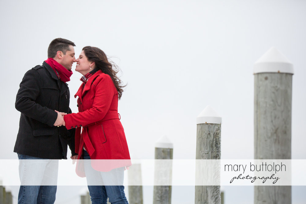 Couple rub noses at the dock at the Aurora Inn Engagement