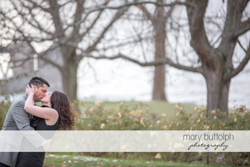 Couple kiss in front of trees in the garden at the Aurora Inn Engagement