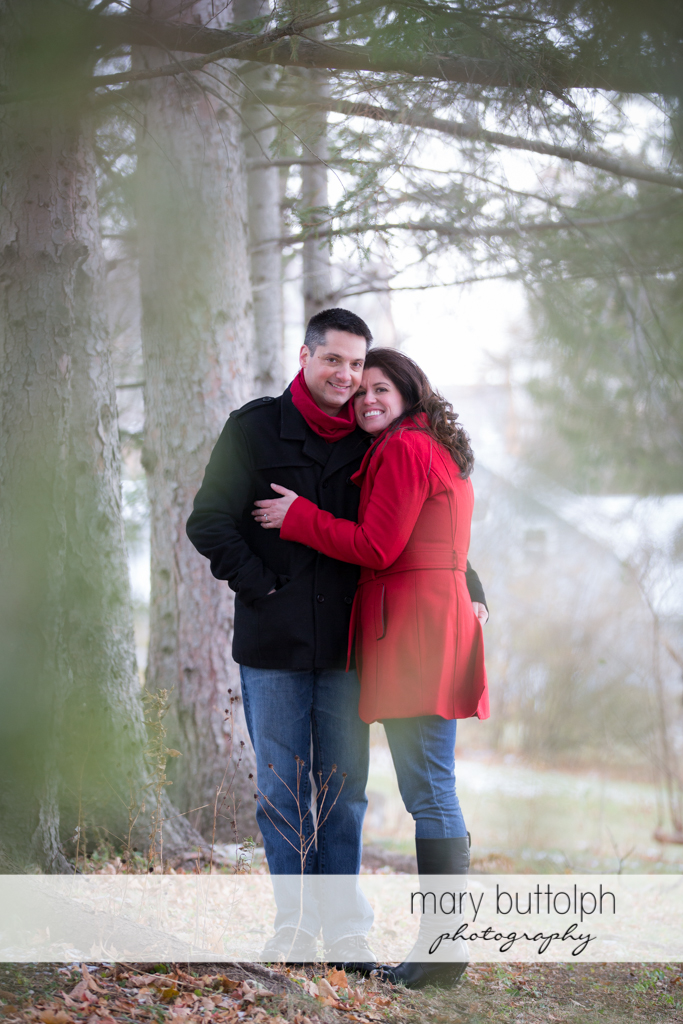 Couple pose near the trees at the Aurora Inn Engagement