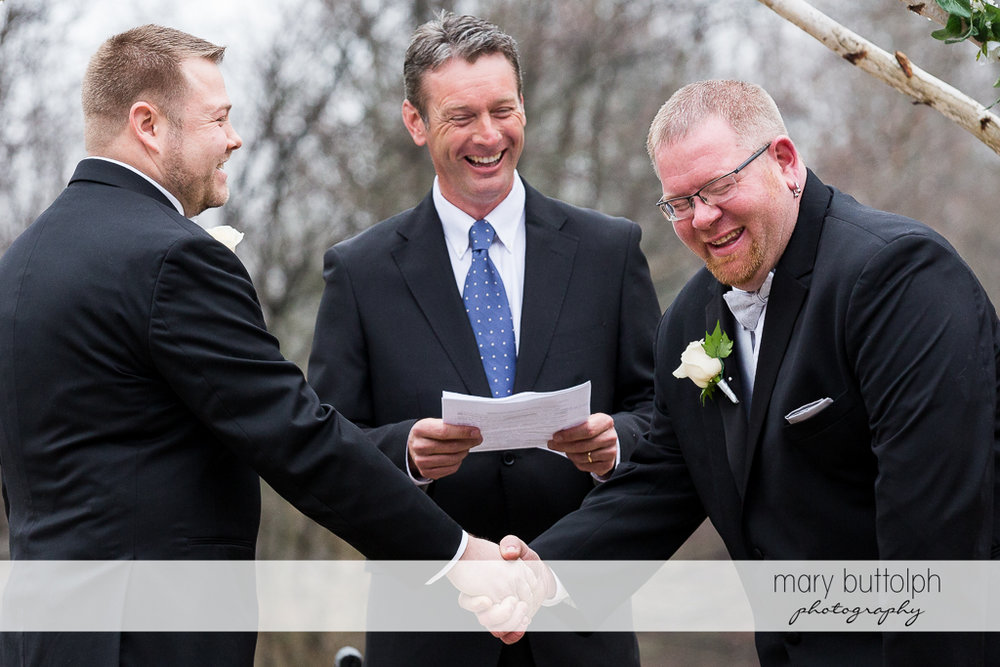 Same sex couple share a good laugh before a wedding officiant at Arrowhead Lodge Wedding