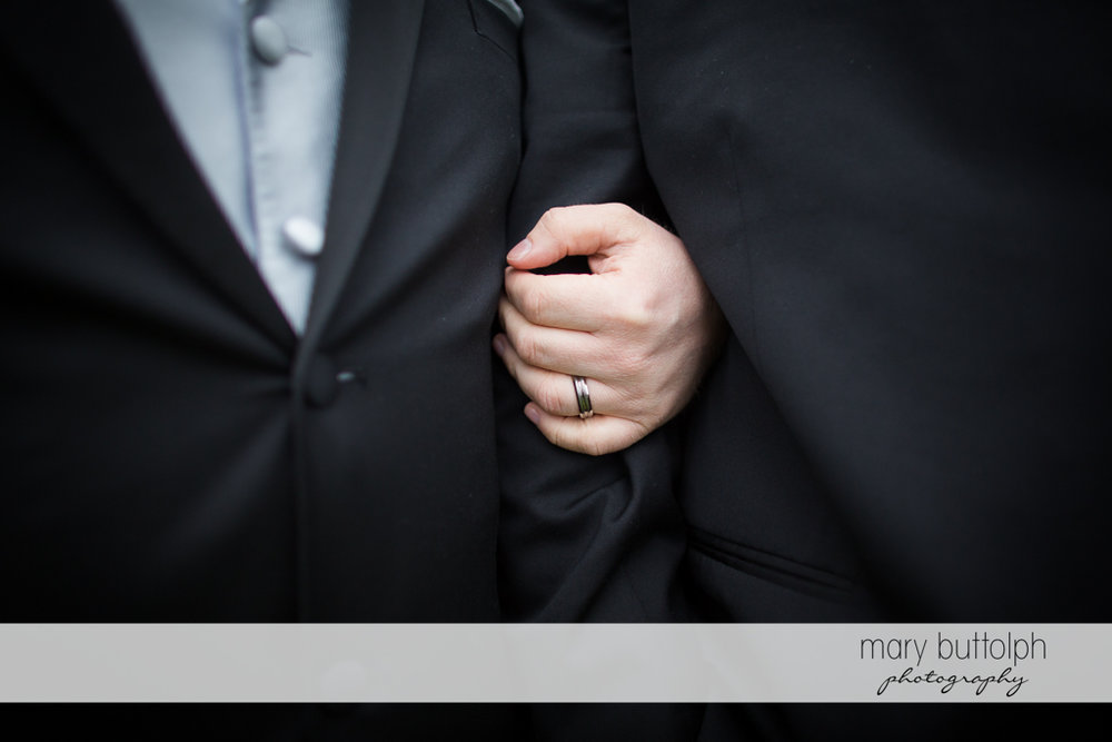 Groom holds his partner's arm at Arrowhead Lodge Wedding