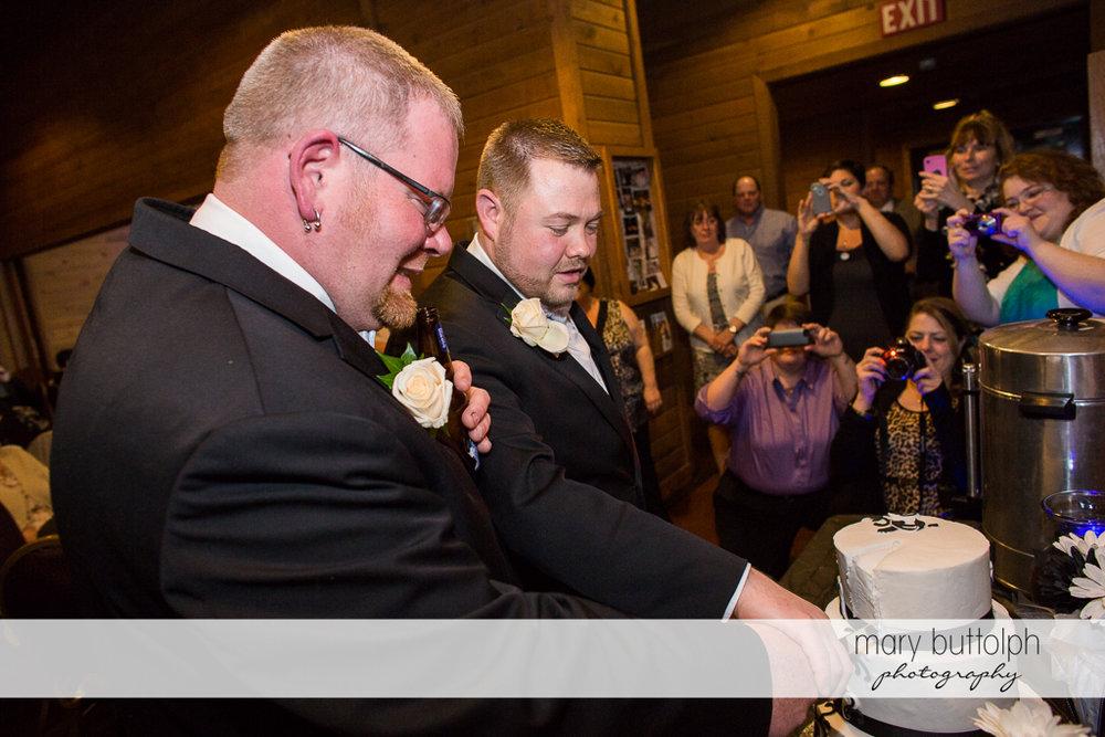 Same sex couple cut their wedding cake at Arrowhead Lodge Wedding
