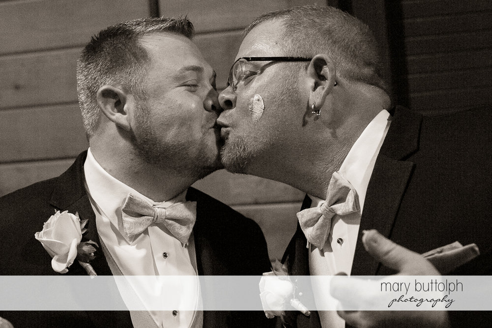 Same sex couple kiss after having cake at Arrowhead Lodge Wedding