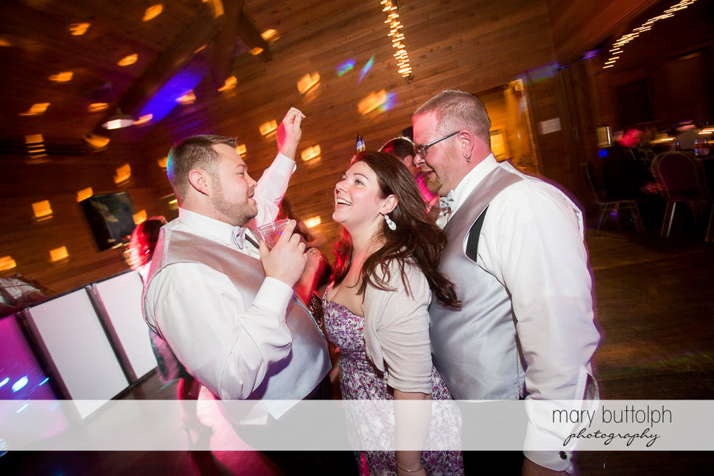 Same sex couple dance with a female guest at Arrowhead Lodge Wedding