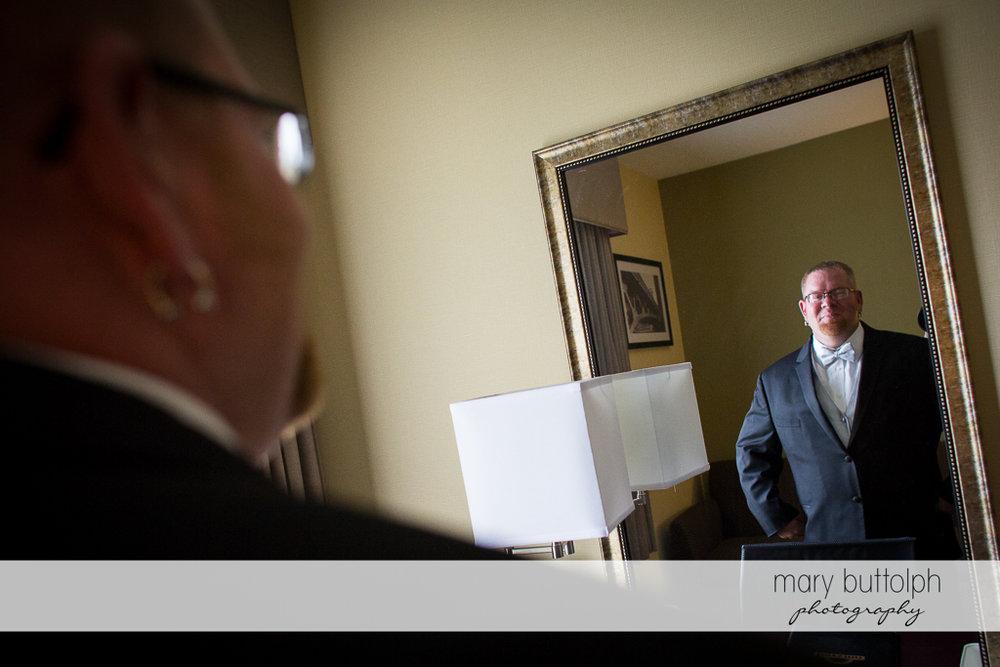 Groom looks in the mirror at Arrowhead Lodge Wedding
