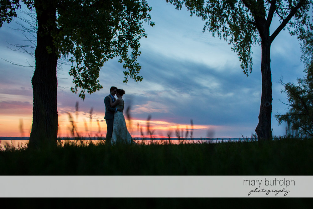 Couple get romantic as the sun sets by the lake at the Inns of Aurora Wedding