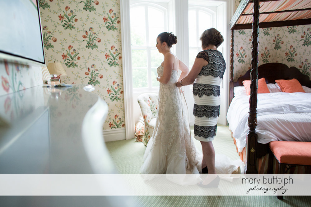 Bride slips into her wedding dress with a little help from her mother at the Inns of Aurora Wedding