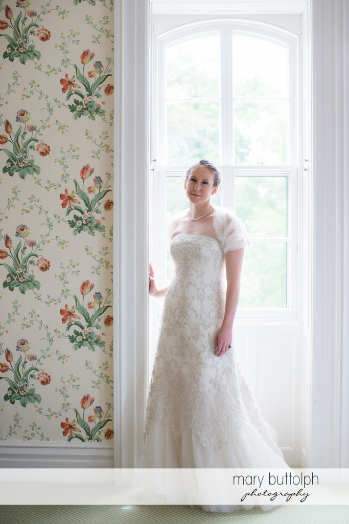 Bride poses by the window at the Inns of Aurora Wedding