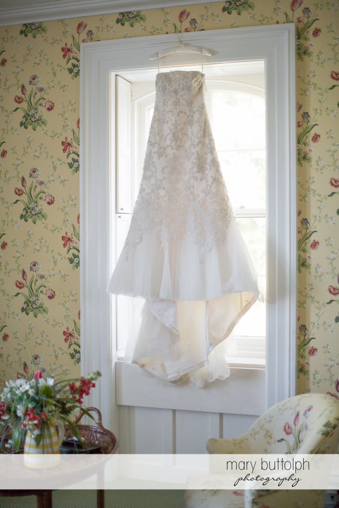 Bride's wedding dress hangs from the window at the Inns of Aurora Wedding