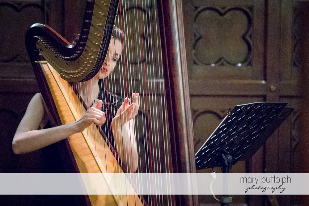 Female harpist provides soothing music in church at the Inns of Aurora Wedding
