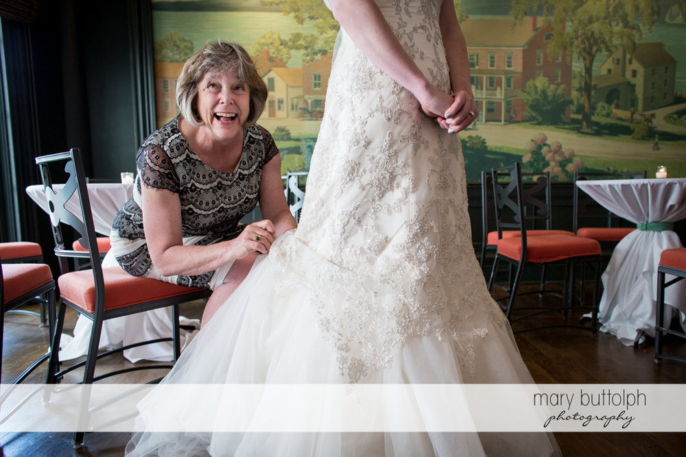 Bride's mother is busy fixing her daughter's wedding dress at the Inns of Aurora Wedding