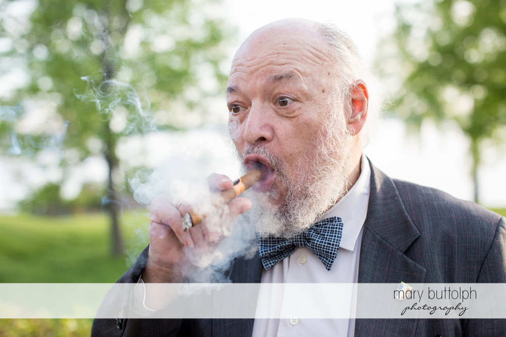 Bride's father smokes a cigar in the garden at the Inns of Aurora Wedding