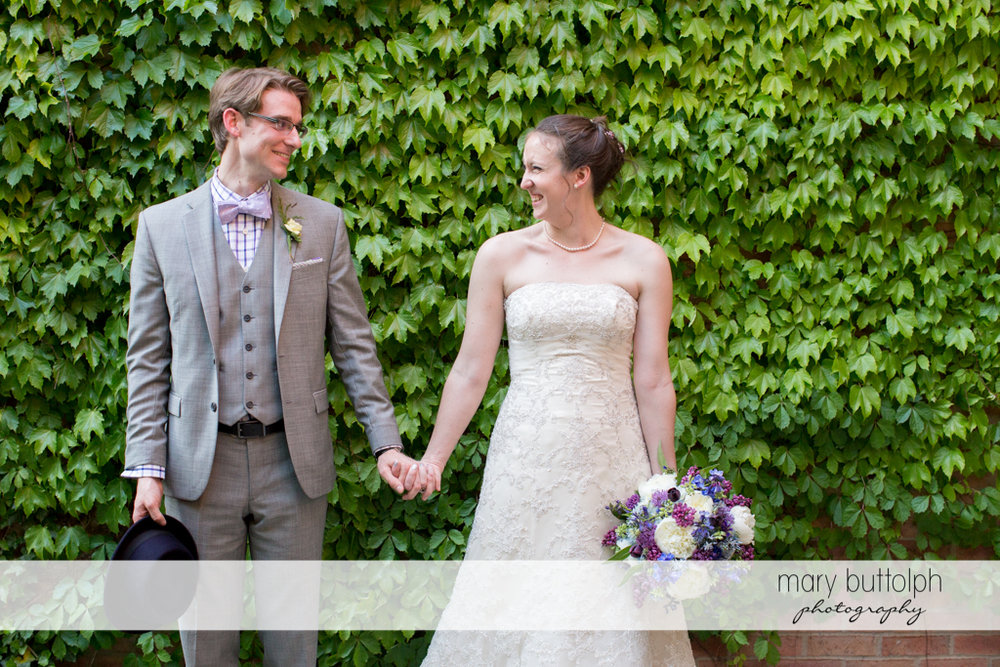 Couple pose in front of a wall of plants at the Inns of Aurora Wedding