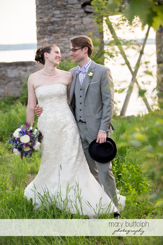 Couple pose near the ruins by the lake at the Inns of Aurora Wedding