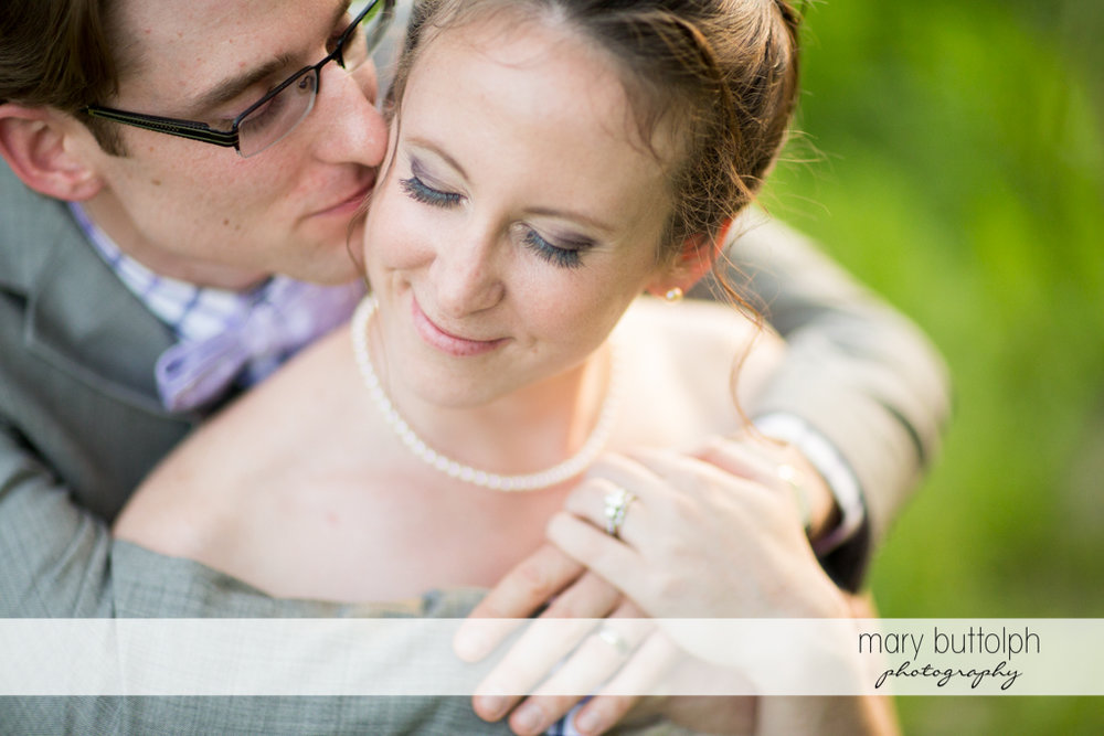 Groom kisses the bride in the garden at the Inns of Aurora Wedding