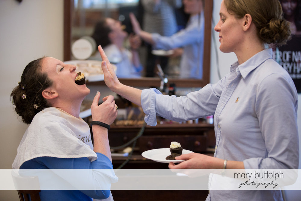 Bride gets a mouthful of cupcake from a friend at the Inns of Aurora Wedding