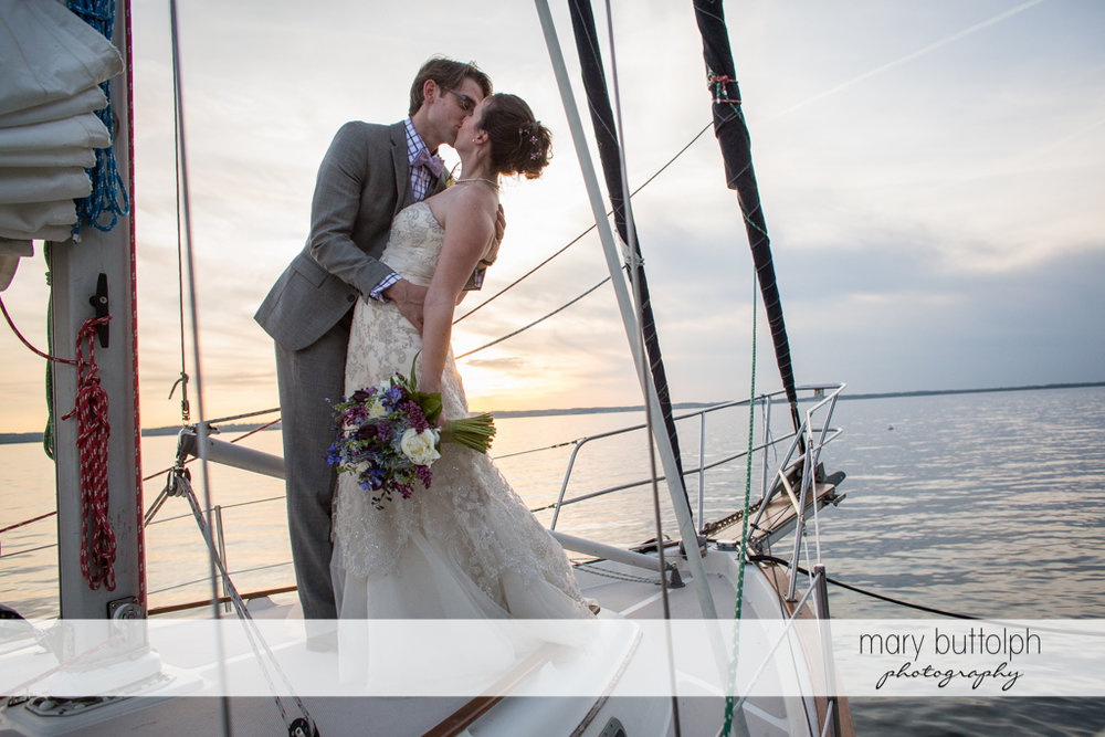 Couple kiss on a sailboat at the Inns of Aurora Wedding