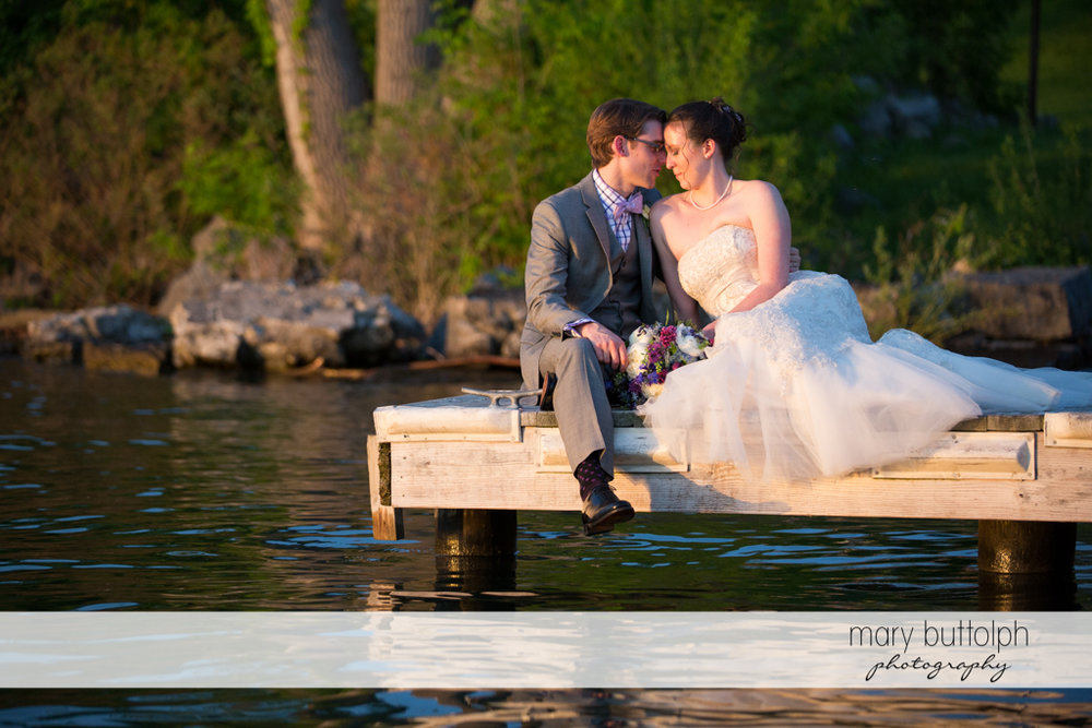 Couple express their love by the lake at the Inns of Aurora Wedding