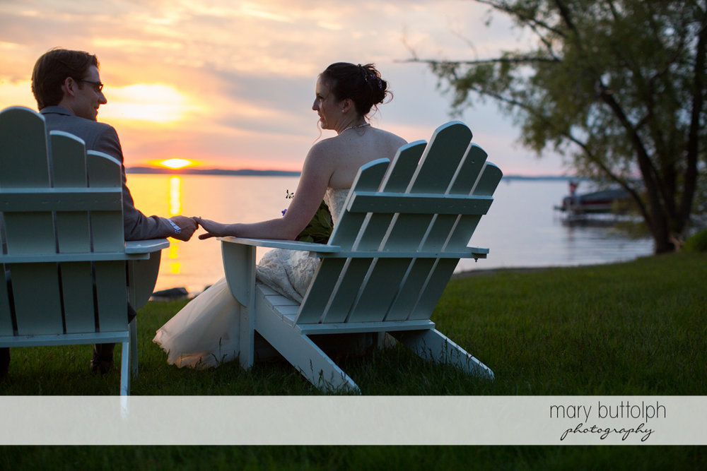 Couple watch the sunset by the lake at the Inns of Aurora Wedding
