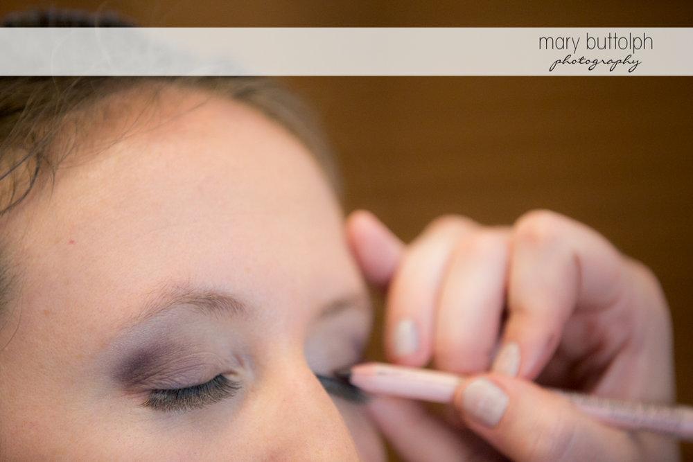 Makeup artist applies eye shadow on the bride at the Inns of Aurora Wedding